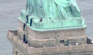 امرأة تتسلق تمثال الحرية وإخلاء المنطقة من الزوار