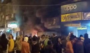 محتجون في طرابلس يضرمون النار عند مدخل مخفر التل